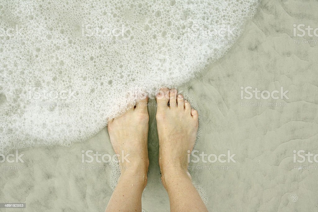 Woman's Feet in Ocean on Beach stock photo
