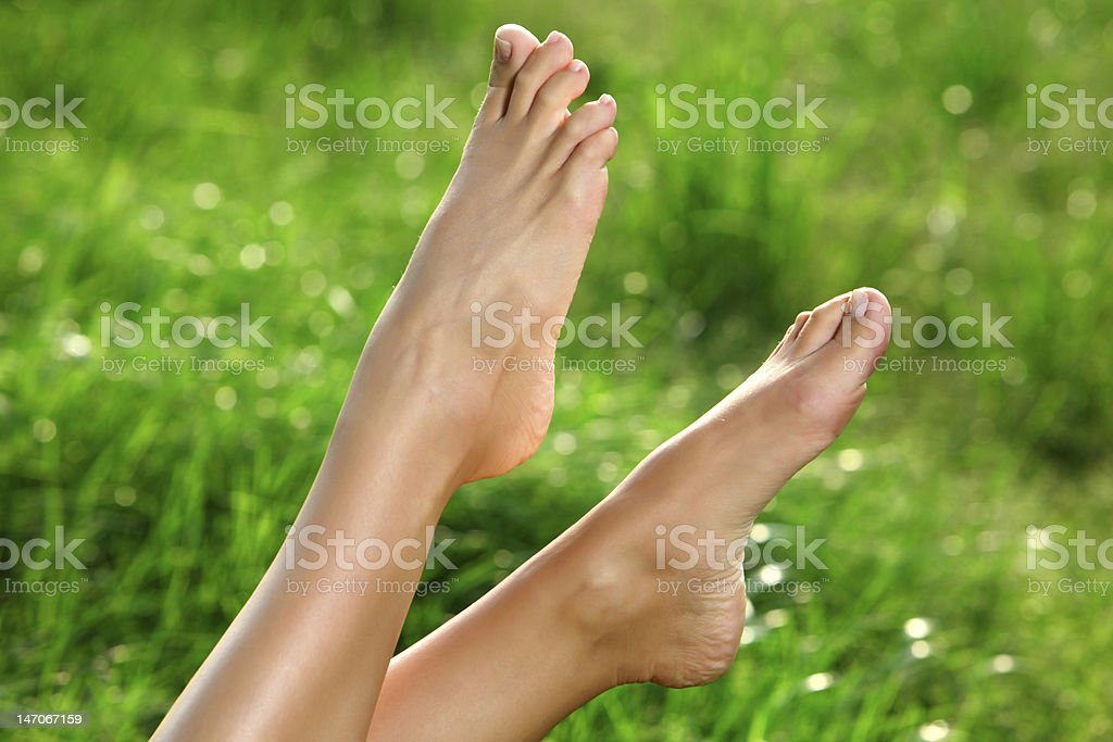 Woman's feet in the air in front of thick grass stock photo