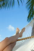 woman's feet in the hammock at the beach