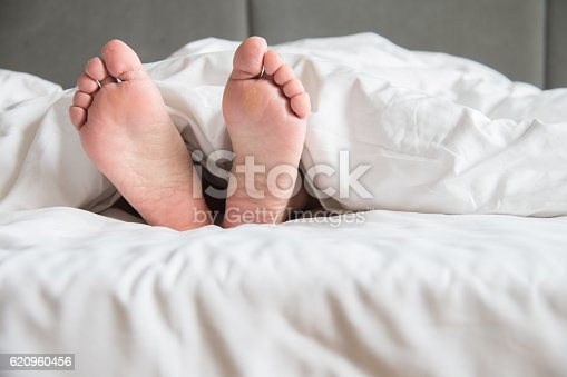 164979632istockphoto Woman's feet in the quilt 620960456