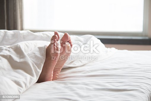 164979632istockphoto Woman's feet in the quilt 620960590