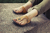 Woman's feet in yellow stylish summer sandals