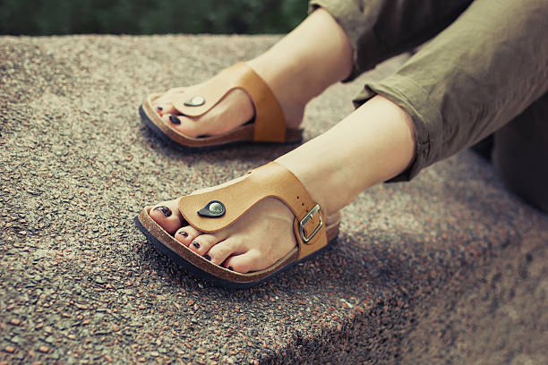 woman's feet in yellow stylish summer sandals - 샌들 뉴스 사진 이미지