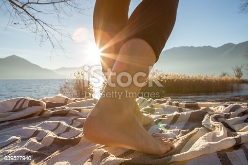 Close up on woman's feet standing on a boat above the lake, sunbeam on the skin.
