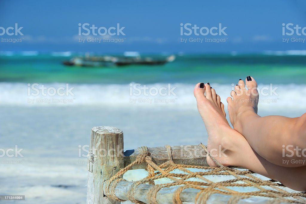Womans feet on a beacht bed the beach royalty-free stock photo