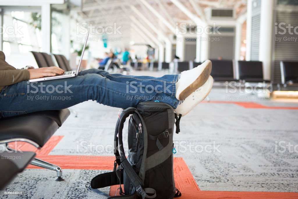 Womans feet on a suitcase in airport stock photo