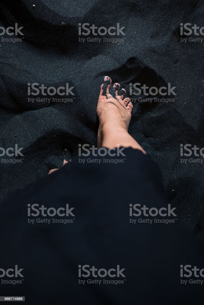 Woman's feet on black sand from above stock photo