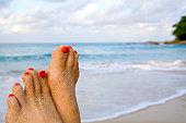 女性の足にビーチ