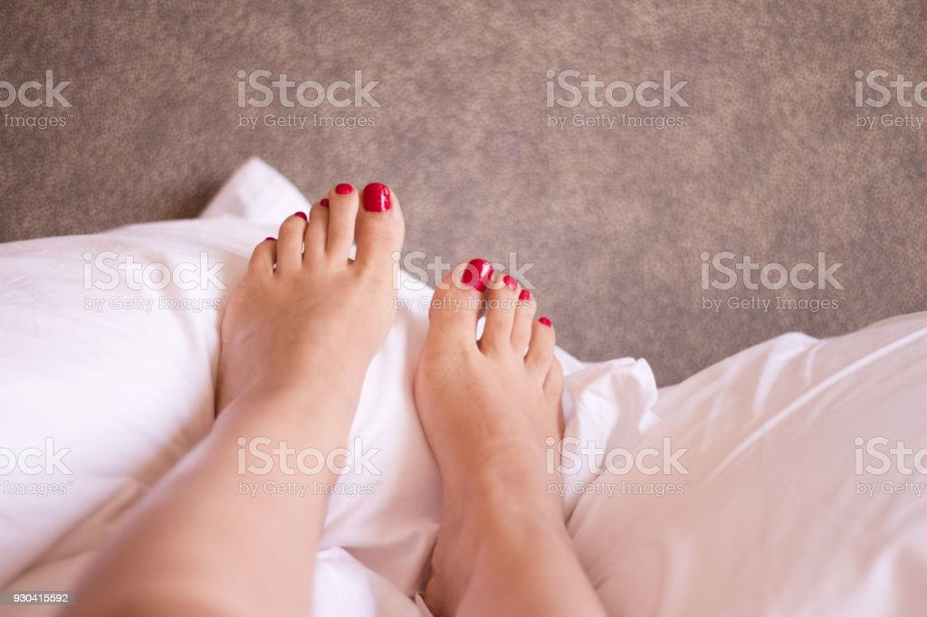 Womans feet on the bed undone. Nails painted red stock photo