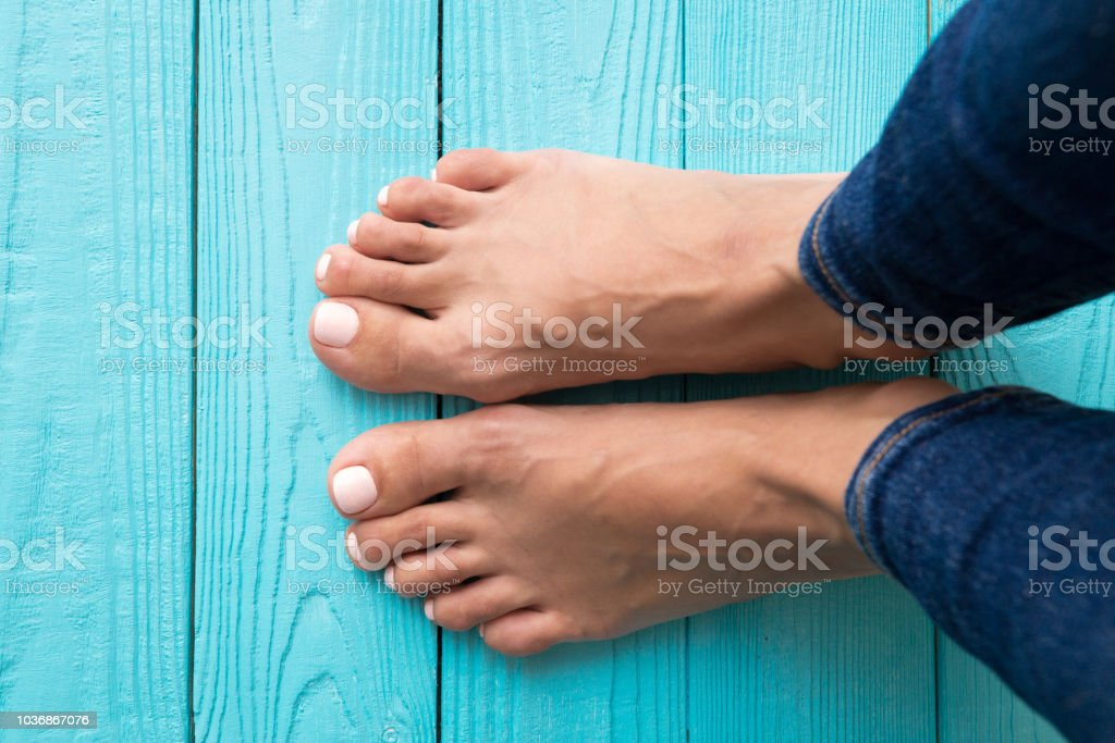 Woman's feet Woman's feet. Girl's feet on wooden floor view from above. 40-44 Years Stock Photo