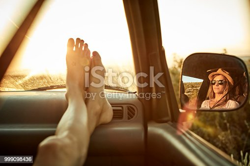 Woman's feet relaxing on dashboard. Reflection of female is on side-view mirror. She is enjoying road trip in mini van during sunset.