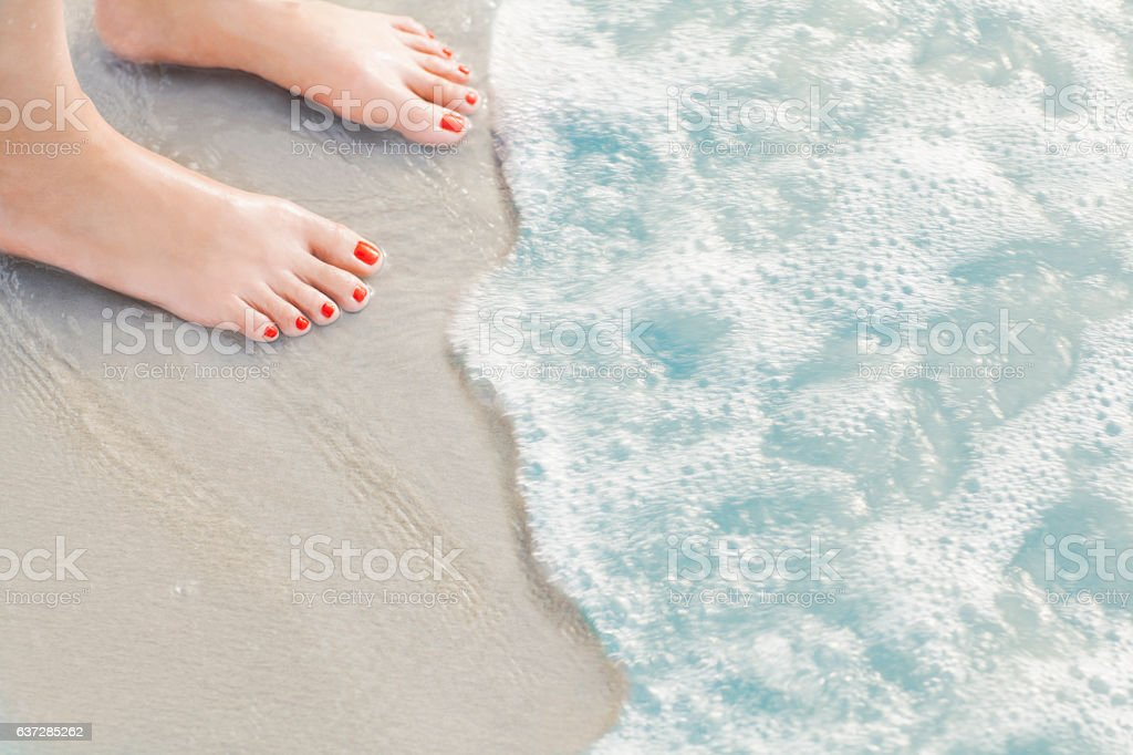 Woman's feet standing in surf at the beach stock photo