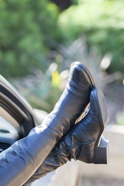 Womans feet sticking out of car window stock photo