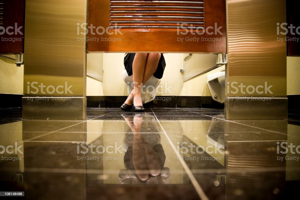 Woman's Feet Underneath Toilet Stall stock photo
