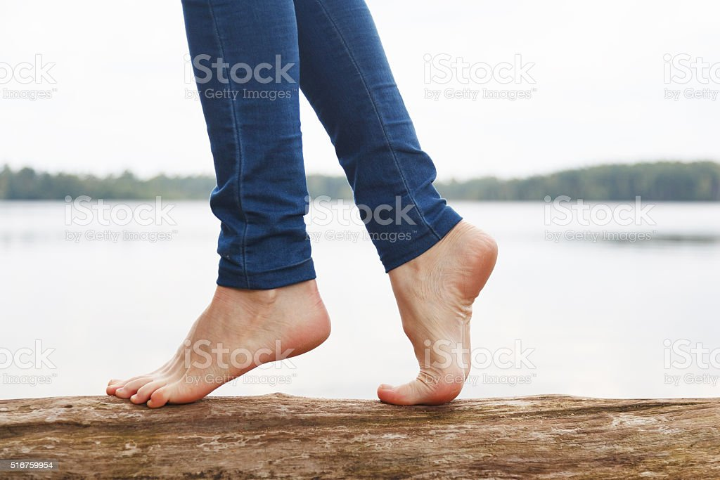 Womans feet walking on a log stock photo