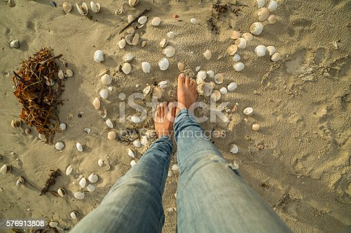 910785546 istock photo Woman's feet walking on seashell by the beach 576913808