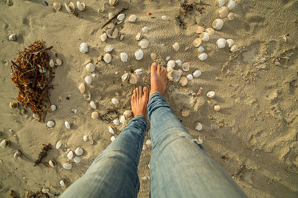 woman's feet walking on seashell by the beach - woman leg beach pov stock photos and pictures