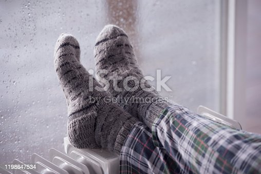 Woman's feet heating up on an oil radiator heater in front of a wet window. Selective focus on gray woolen socks. A woman staying at home in the rainy winter season.