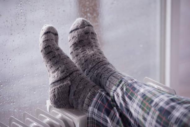 Woman's feet wearing gray woolen socks, warming cold feet on oil heater in the rainfall winter season. stock photo