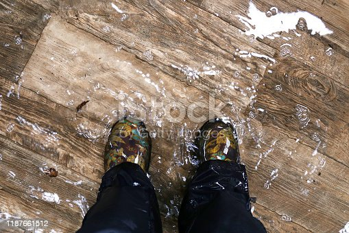 A woman's feet, wearing waterproof rain boots are standing in a flooded house with vinyl wood floors.