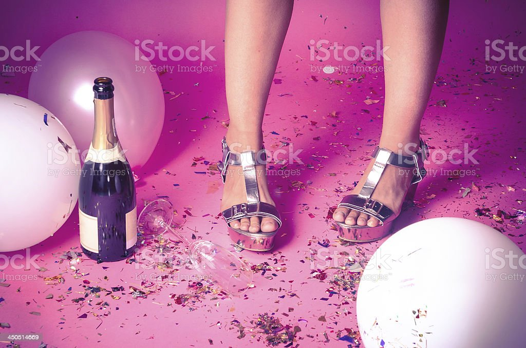 Woman's feet with confetti on the floor and champagne stock photo