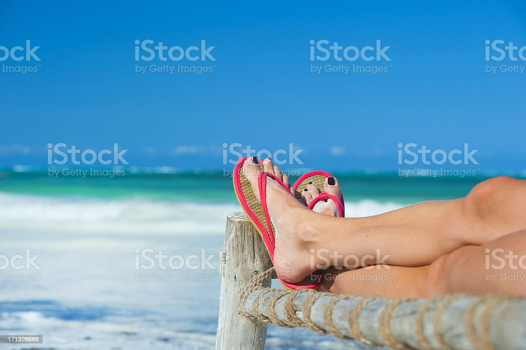 Womans feet with flip-flops at the beach royalty-free stock photo