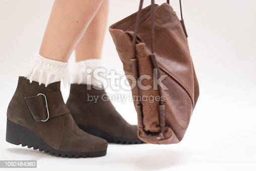 Woman's Feet/Legs in Fancy Shoes and Lace Socks. She's walking, and a purse hangs down near the shoes. White background with copy space.