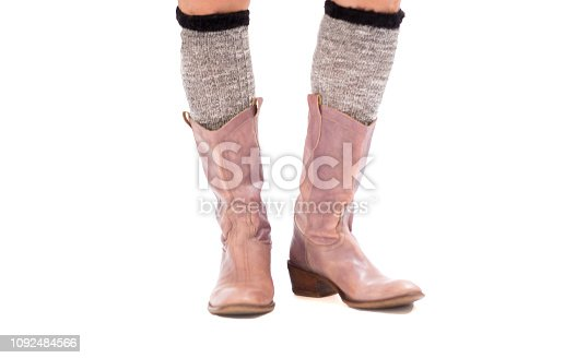 Woman's feet/legs in socks and purple cowboy boots. White background with copy space at the bottom of the frame. Close-up shot.