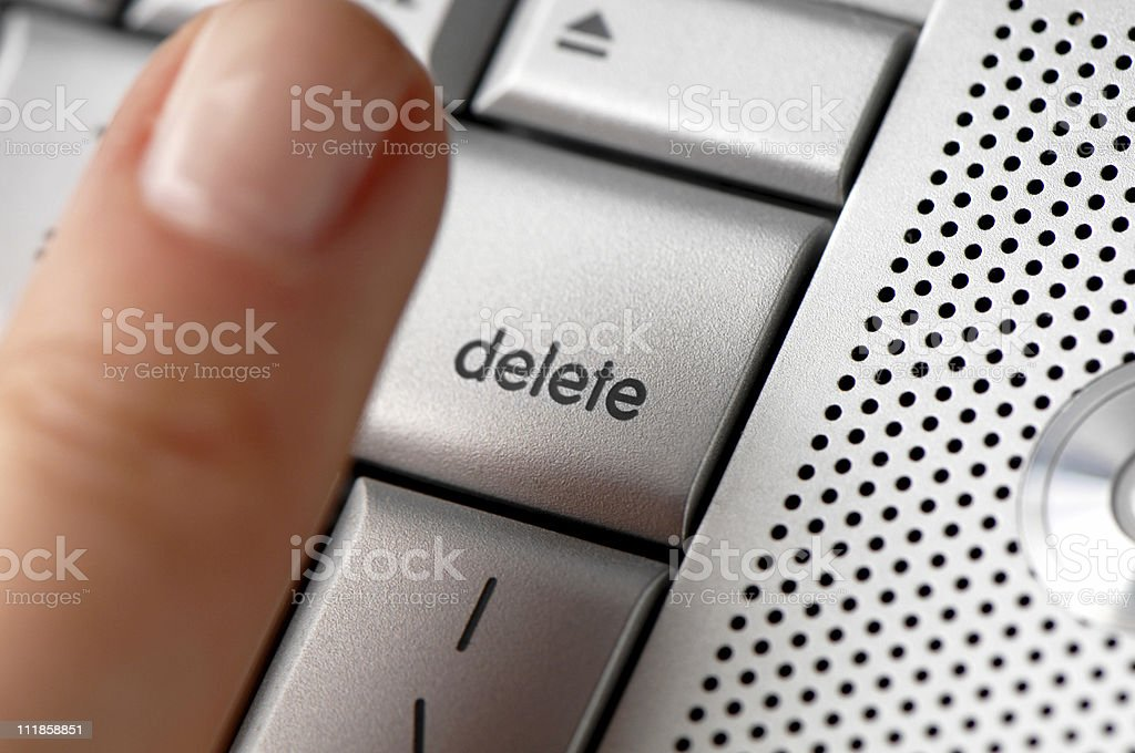 Woman's Finger Hovers Over Delete Key on Laptop Computer stock photo