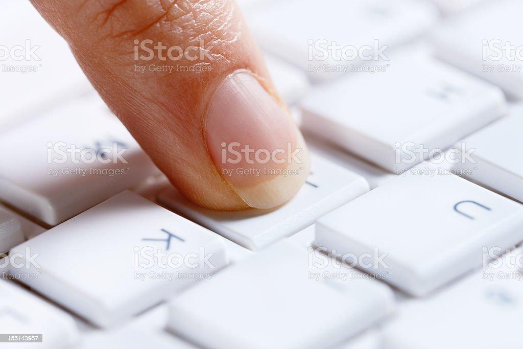 Woman's finger presses key on white pc keyboard stock photo