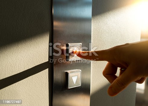 a woman's finger presses the Elevator button in the sunlight