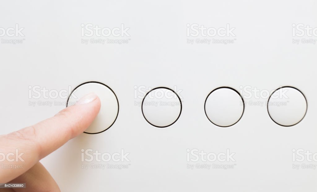Woman's finger push the white button on the appliance. stock photo