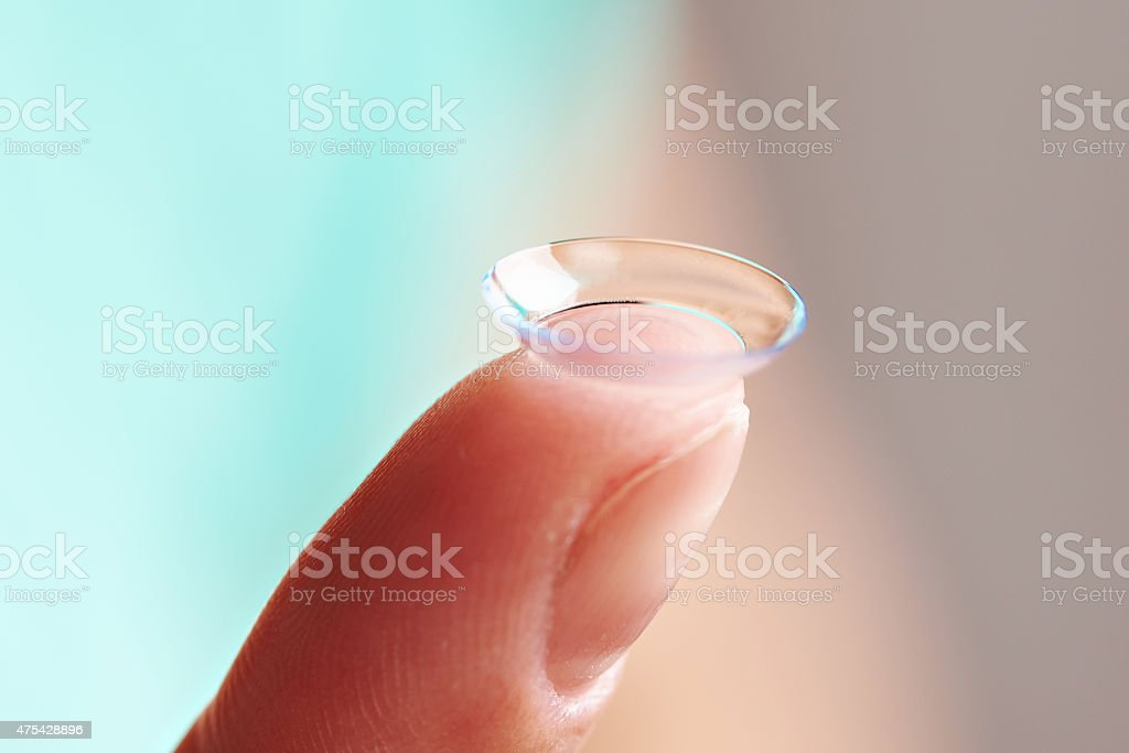 Womans finger with contact lens stock photo