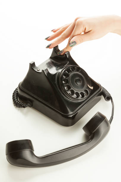 Woman's fingers dialing a vintage rotary dial telephone stock photo