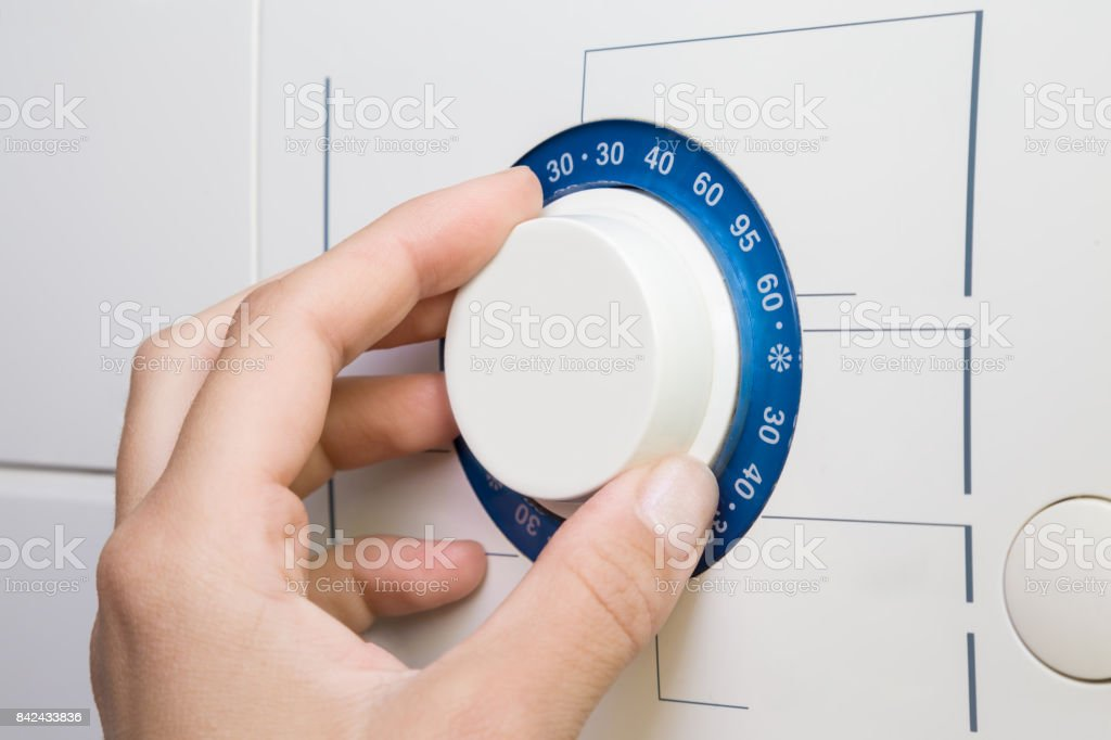 Woman's fingers turning the temperature button on the washing machine. Preparing washing a clothes. stock photo