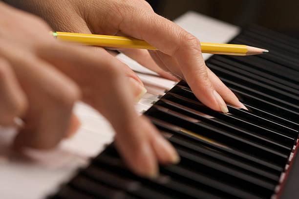 weiblichen finger mit bleistift auf piano-schlüssel - kreatives schreiben übungen stock-fotos und bilder