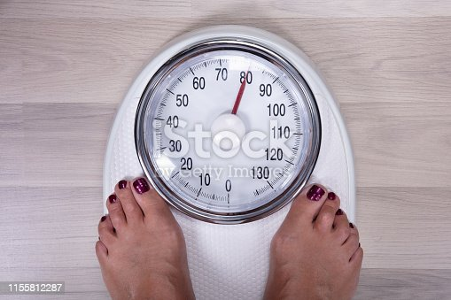 An Overhead View Of Woman's Foot On Weighting Scale Over The Hardwood Floor