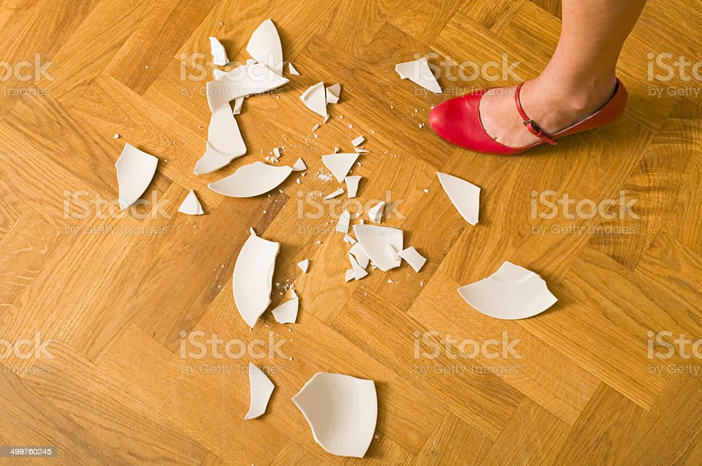 womans foot stamping on plate in a rage stock photo