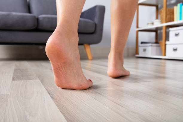 woman's foot walking on hardwood floor - scalzo foto e immagini stock