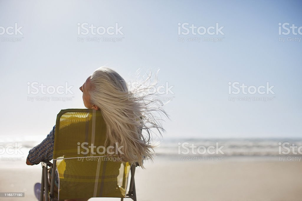 Womans hair blowing in wind on beach stock photo