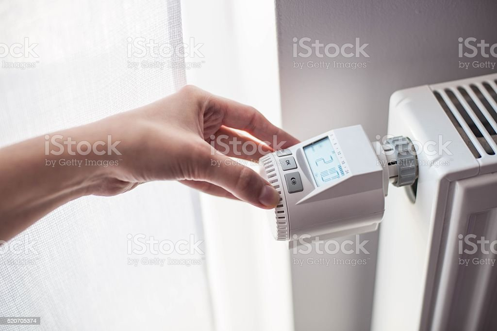 Woman's hand adjusting temperature stock photo