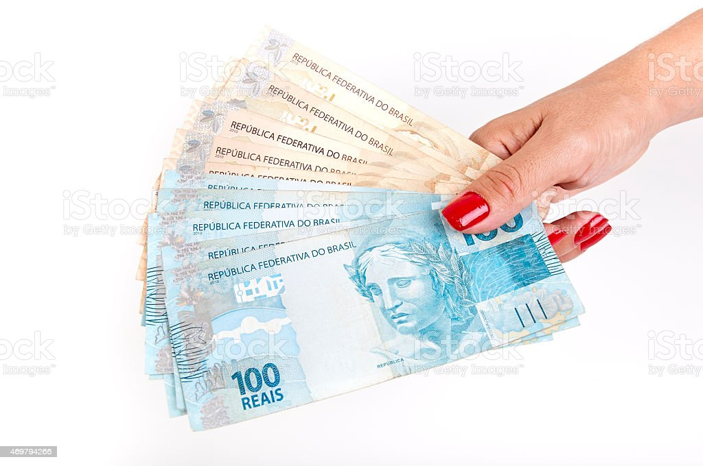 Woman's hand and Brazilian money stock photo