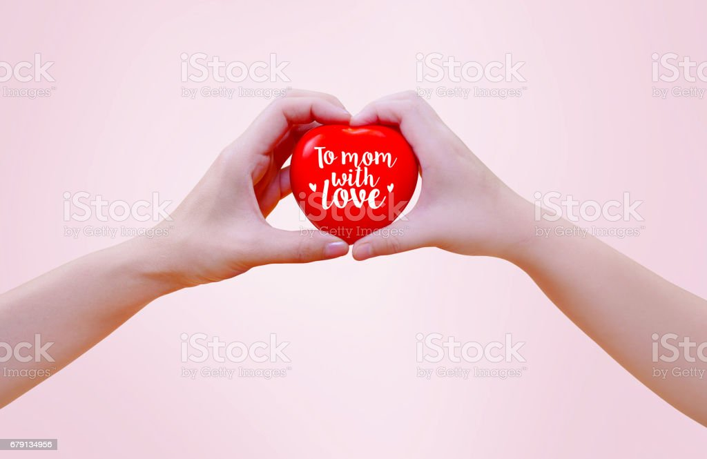 Woman's hand and girl kid's hand holding a red heart on pink background together, to mom with love concept. Mother'u2019s day. photo libre de droits