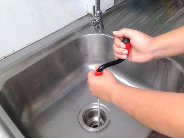 kvinnans hand bryter igenom rören. täppa pipe cleaner själv. flexibel fjäder avlopps renare. - penetrating bildbanksfoton och bilder