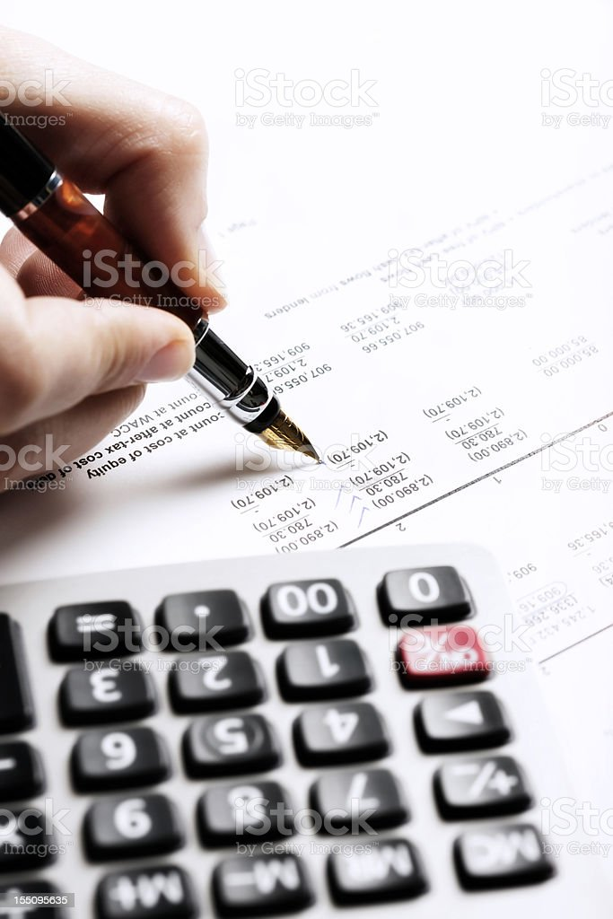 Woman's hand checks financial spreadsheet with calculator standing by royalty-free stock photo