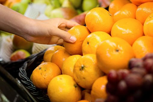 woman's hand choosing orange in supermarket