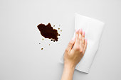Woman's hand cleaning fresh spilled dark beverage from gray desk. Coffee stain simple removing with white paper napkin. Cleanup. Close up. Top view.