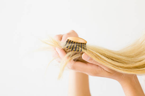 Woman's hand combing blonde hair on the light gray background. Hair problem and solution. Daily preparation for good looking. Women's issues. stock photo