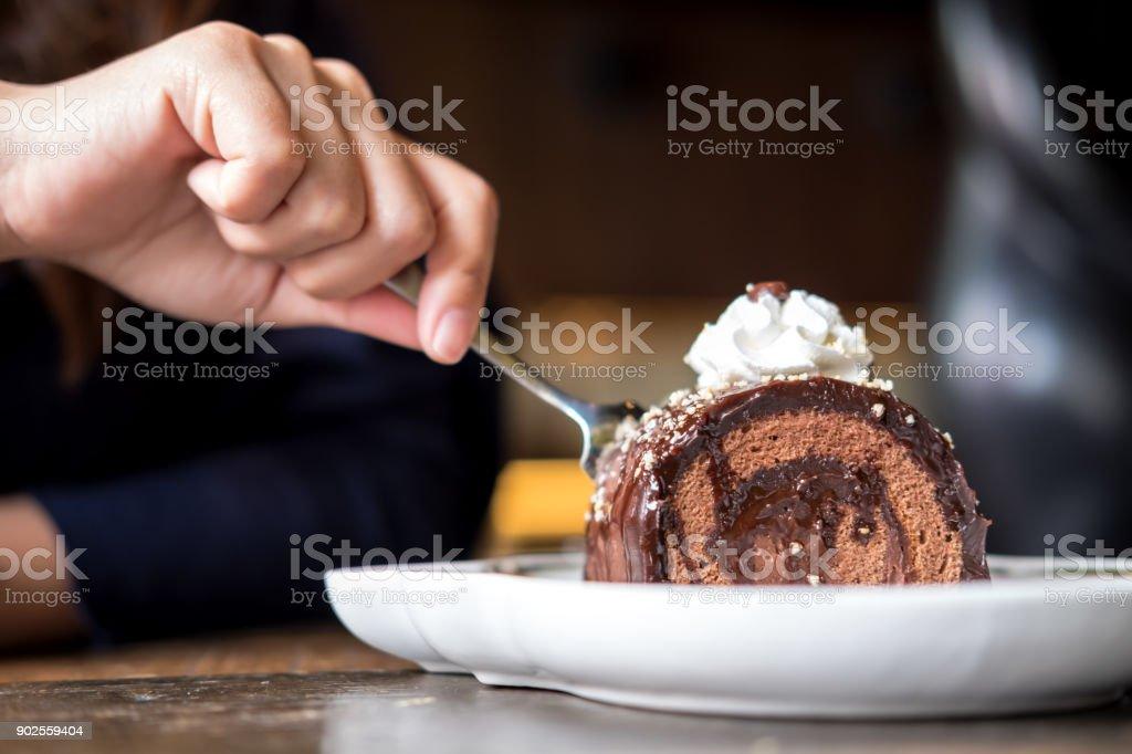Corte da mão de uma mulher chocolate bolo de rolo e chantilly em cima com garfo no café de madeira vintage - foto de acervo
