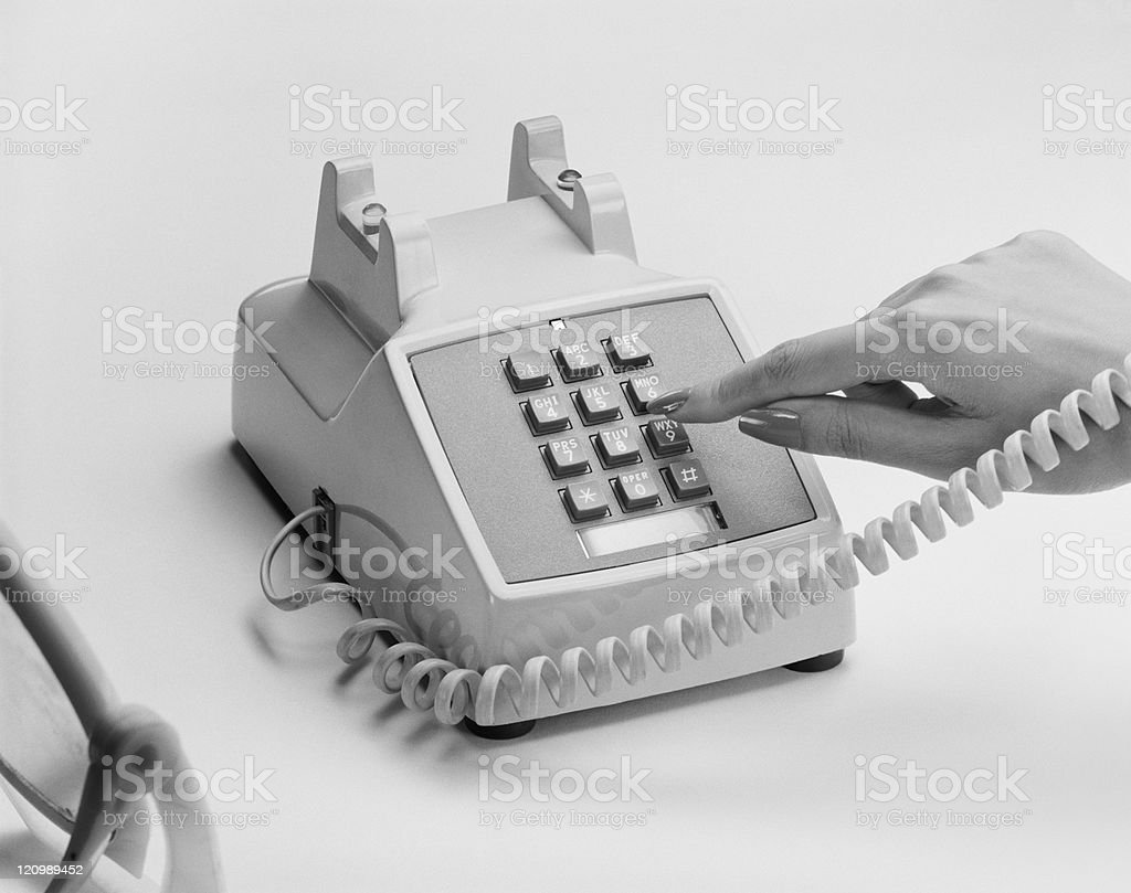 Woman's hand dialling telephone number, close-up stock photo
